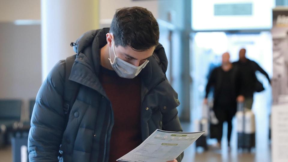 À son arrivée à l'aéroport Billy Bishop de Toronto, un voyageur consulte un dépliant de santé concernant la COVID-19.