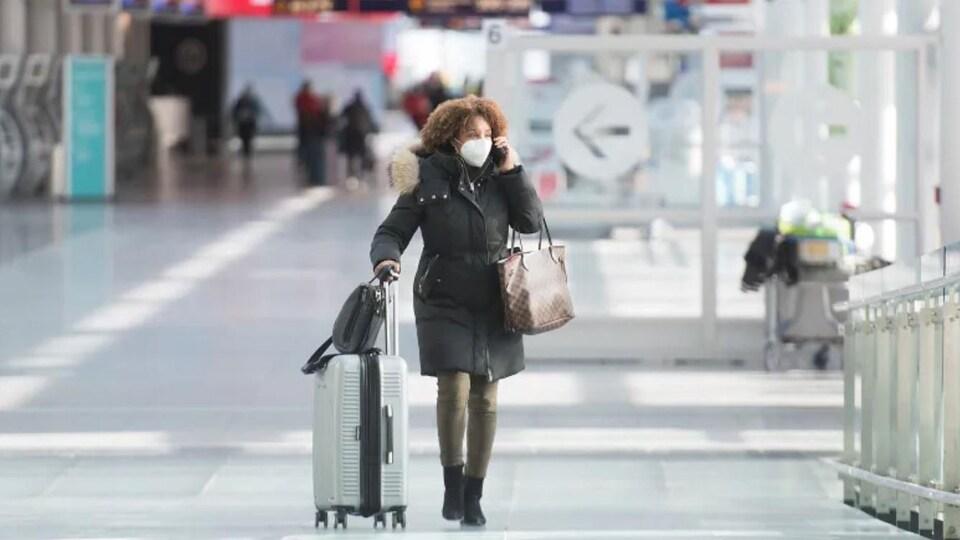 Un passager porte un masque facial alors qu'il traverse l'aéroport international Montréal-Trudeau.