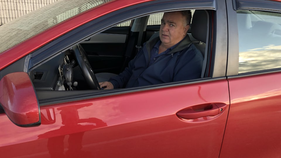 Il est assis dans sa voiture devant l'aéroport.