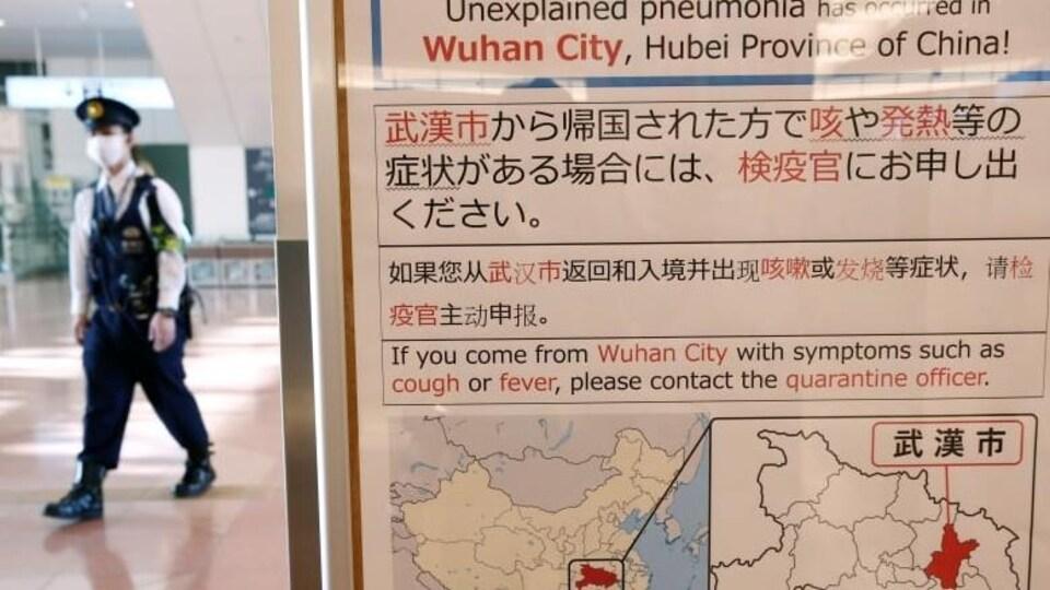 Un panneau qui montre la ville de Wuhan en Chine et qui mentionne que si les voyageurs arrivent de cette ville et qu'ils ont de la toux ou de la fière, il faut en informer le personnel immédiatement.
