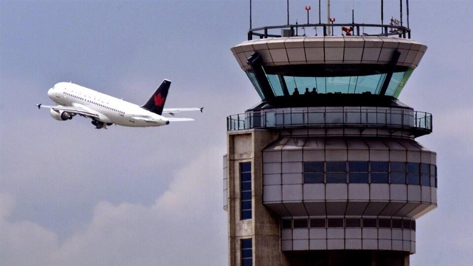 Un avion contourne la tour de contrôle de l'aéroport Pierre-Elliott-Trudeau (archives).