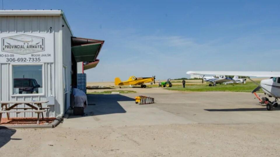 Quelques avions stationnés à l'aéroport de Moose Jaw, tout près d'un petit bâtiment.
