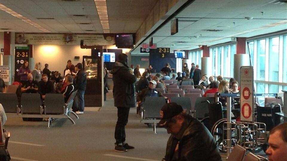 Intérieur de laéroport international de Thunder Bay avec des gens qui attendent.