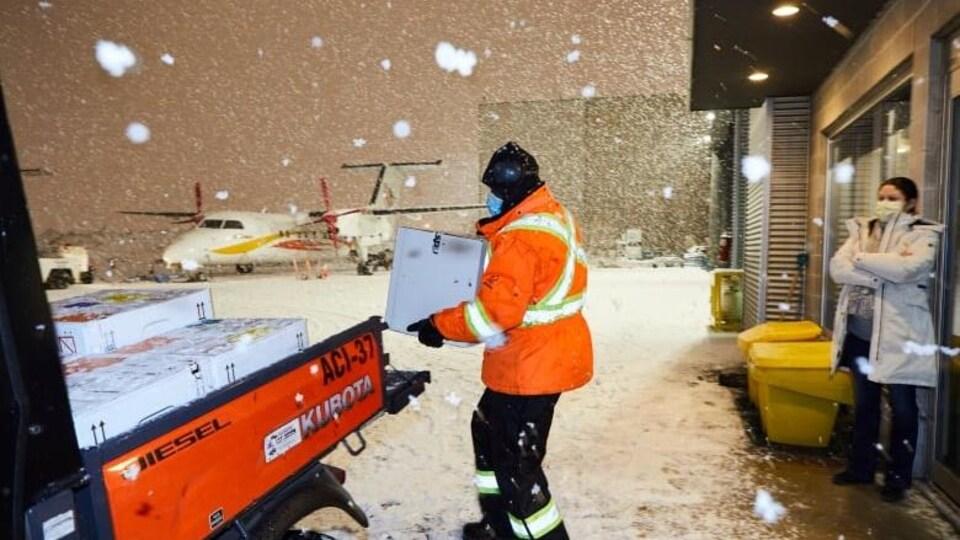 Un employé charge des colis dans un camion sur le tarmac d'un aéroport.