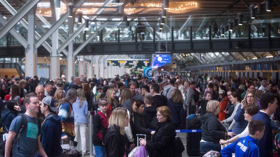 Un nombre important de voyageurs font la queue à l'aéroport international de Vancouver.
