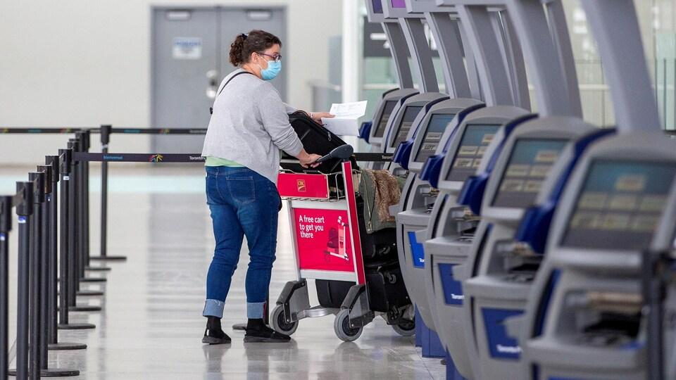Une personne à l'aéroport pousse un chariot.