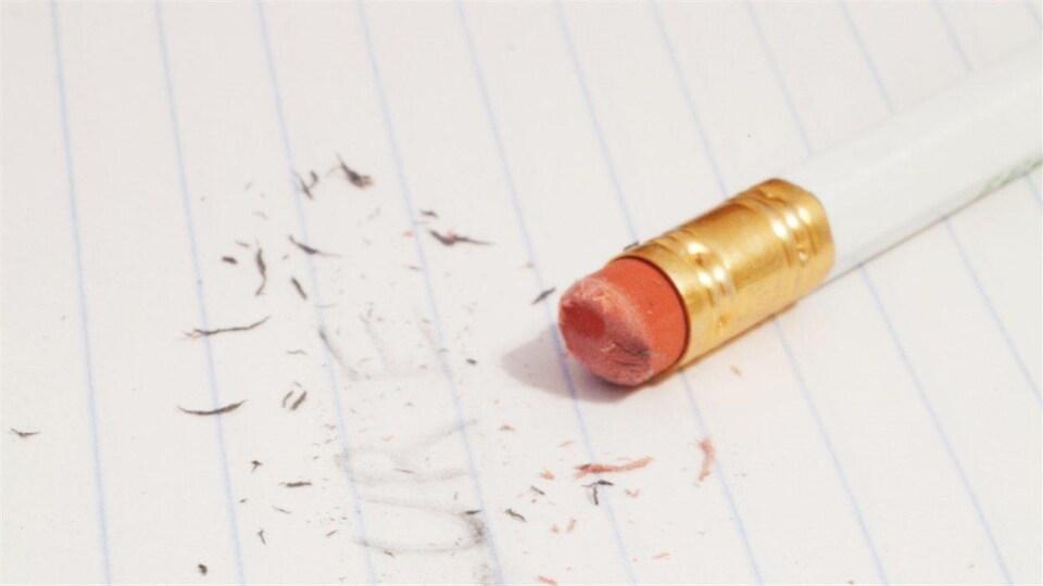 Un mot écrit au crayon effacé sur une page, le crayon est posé sur la page