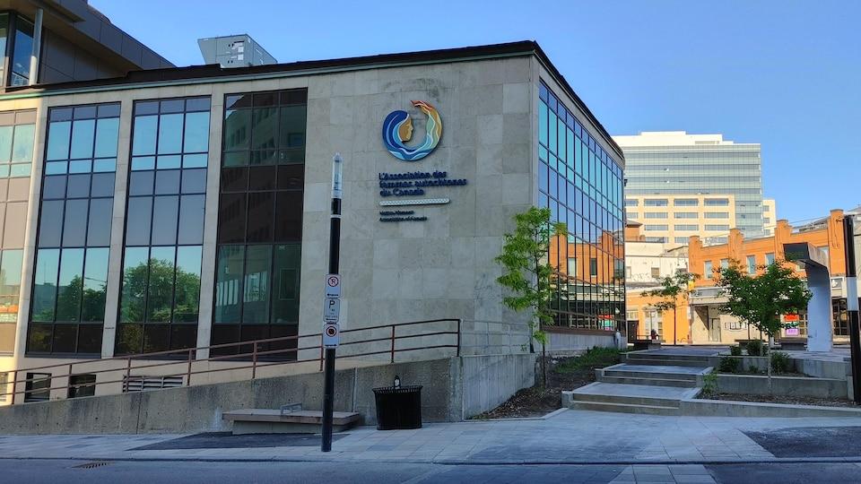 Un bâtiment vitré et de pierres grises avec le logo de l'association.