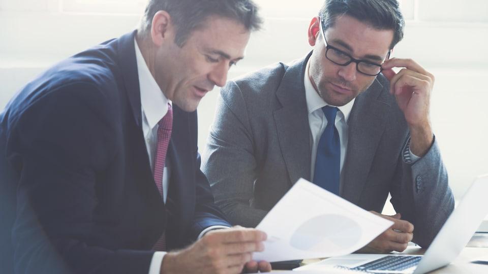 Deux hommes analysent un graphique sur une feuille de papier.