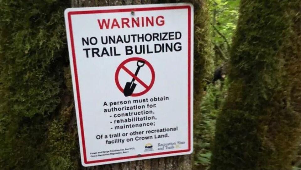 Un avertissement posé sur un arbre.