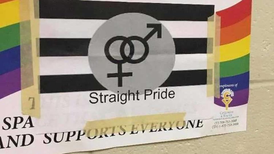 Affiche proclamant la «fierté hétérosexuelle» collée sur une affiche arborant le drapeau arc-en-ciel.