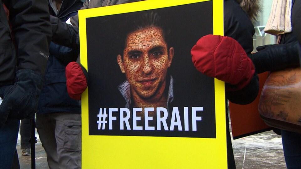 Une affiche montrant Raif Badawi, tenue par une personne.