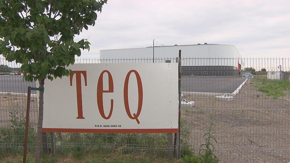 Une affiche où on peut lire TEQ sur une côture devant le Colisée.