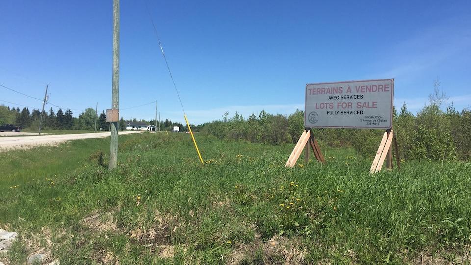 Une affiche indiquant des terrains à vendre.