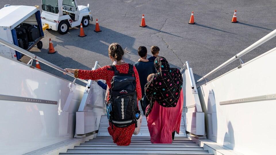Des gens vus de dos descendent d'un avion.