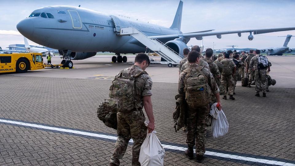 Les militaires américains marchent en rang vers un avion sur le tarmac.