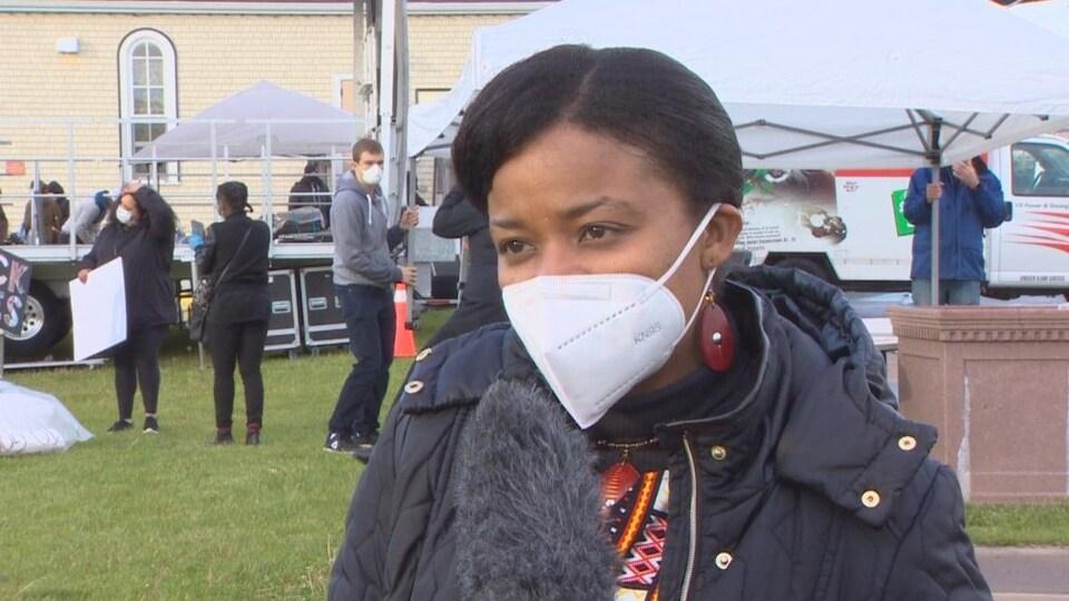 Une femme portant un masque en entrevue.