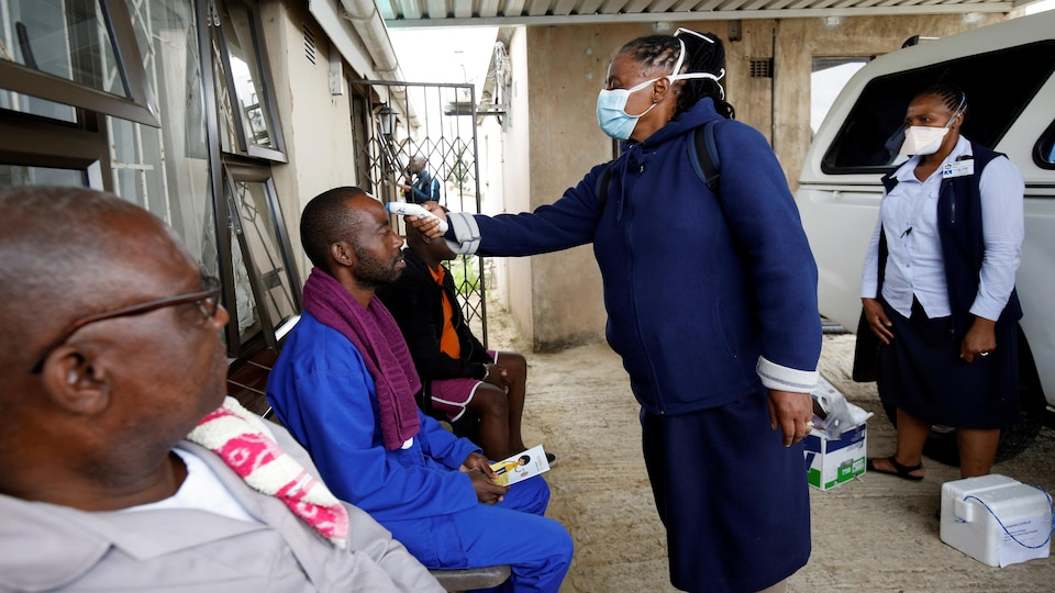 FILE PHOTO: A health worker checks a man's temperature during a door-to-door testing in an attempt to contain the coronavirus disease (COVID-19) outbreak, in Umlazi township near Durban, South Africa, April 4, 2020. REUTERS/Rogan Ward/File Photo - RC231G9W9G1U