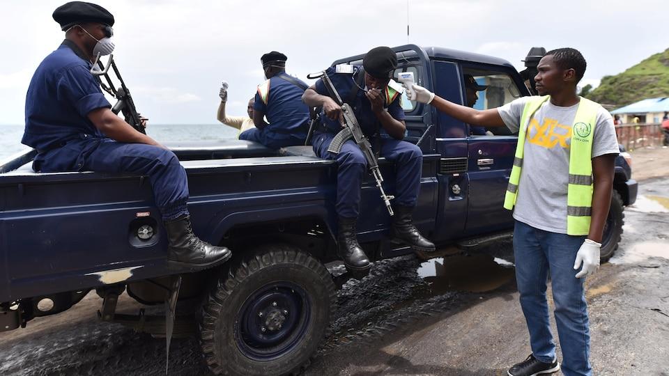 Trois policiers assis sur l'arrière d'un camion et un homme prend la température de l'un d'eux.