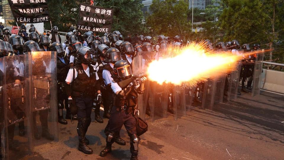 Un policier en armure tire une grenade lacrymogène.