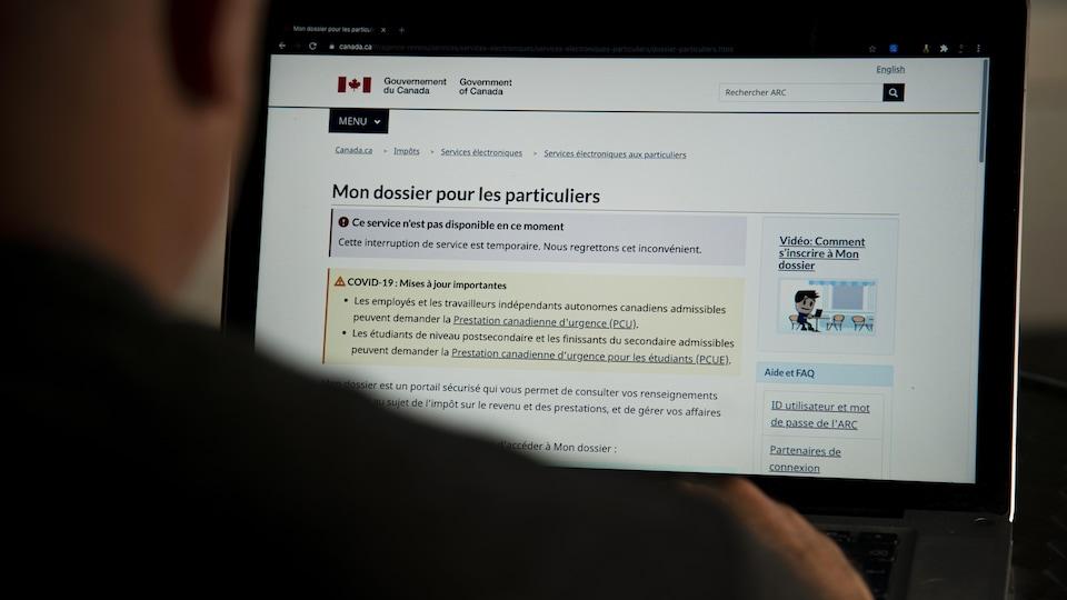 Une personne regarde le site de l'Agence du revenu du Canada sur un écran. La page lui indique qu'elle ne peut consulter son dossier de façon temporaire.