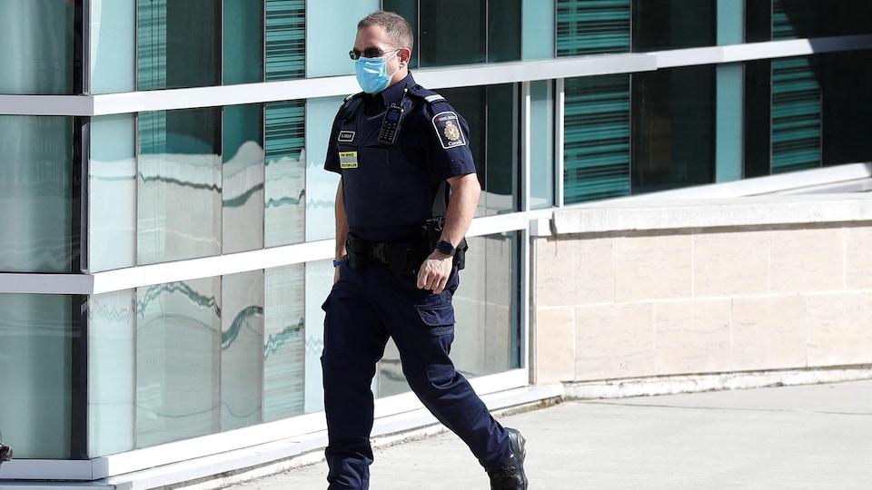 Un agent de l'Agence des services frontaliers du Canada  qui marche, en uniforme, portant un masque et des verres fumés.