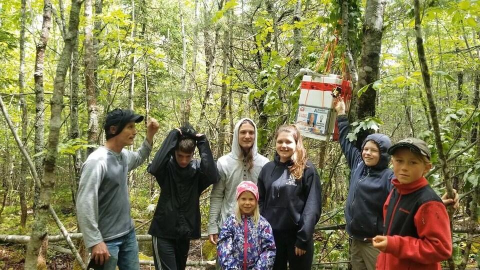 Les jeunes autour de la boîte suspendue à un arbre.