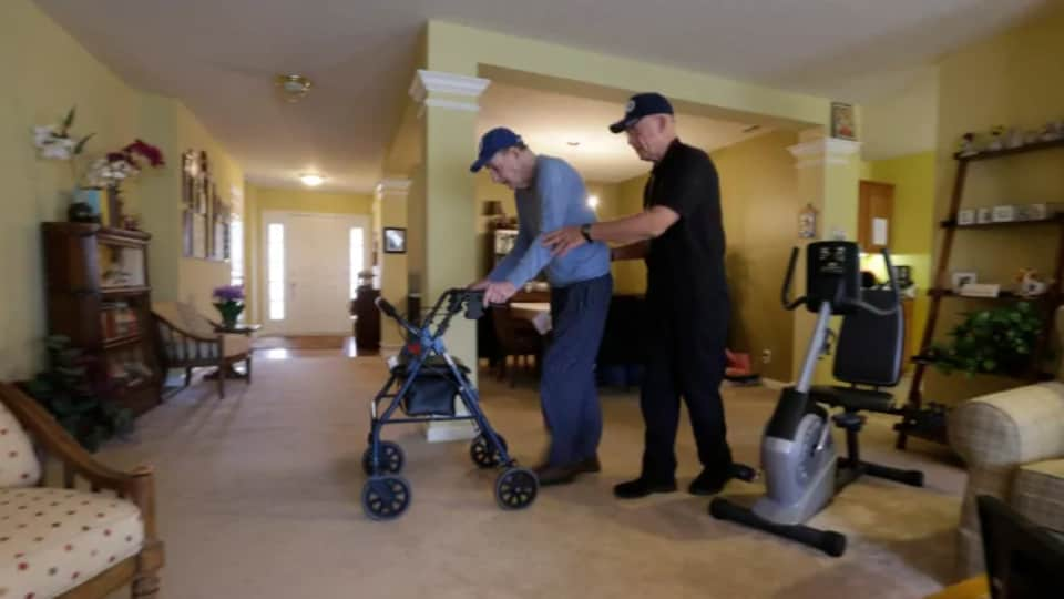 Un employé aide un vieil homme à utiliser une marchette chez lui