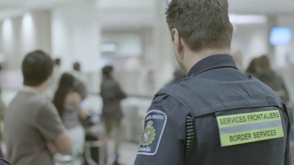 Un agent de services frontaliers observe des voyageurs dans l'enceinte d'un aéroport.