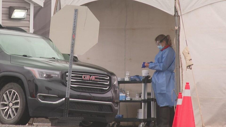 Un agent de la santé publique se prépare à réaliser un test de dépistage rapide de la COVID-19.