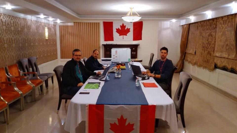 Trois hommes sont assis autour d'une table décorée d'un drapeau canadien.