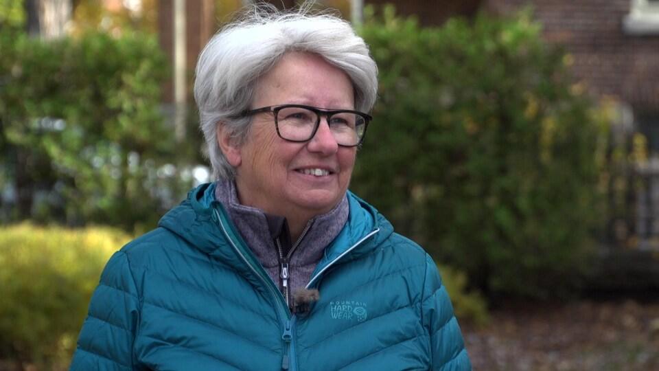 Plan rapproché d'Agnès Maltais, à l'extérieur. Elle porte un manteau bleu et des lunettes.