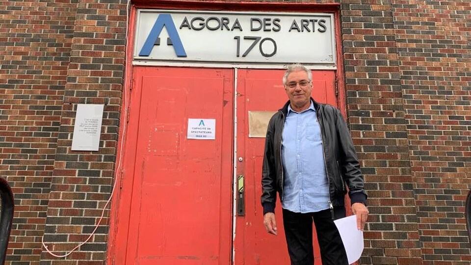 Un homme se tient de bout dans les marches de l'église où se situe l'Agora des Arts. Il tient une feuille dans une main.