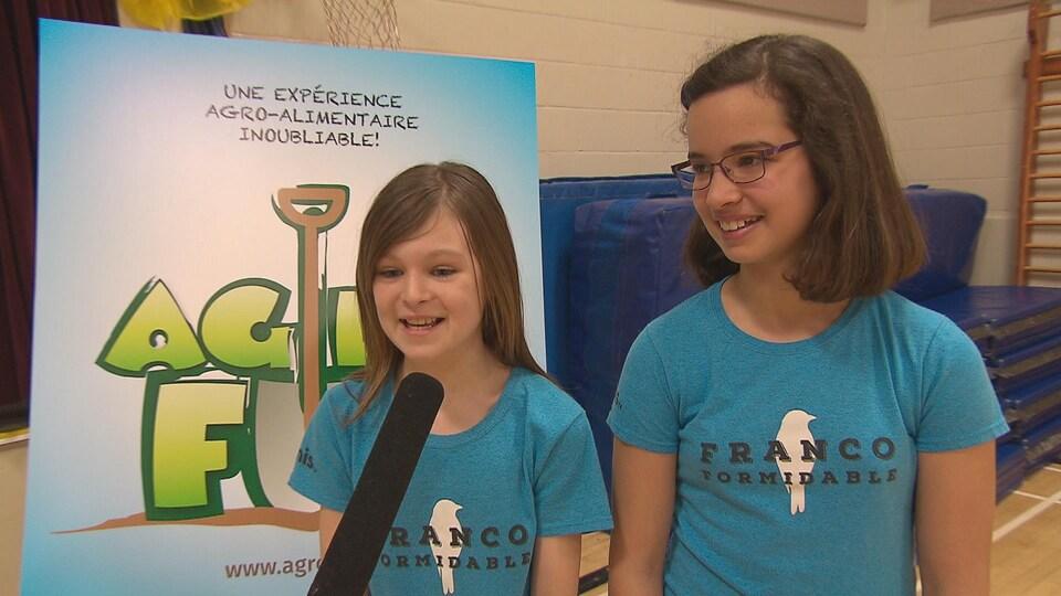 Les deux jeunes filles répondent aux questions. Elles portent un chandail de l'émission.
