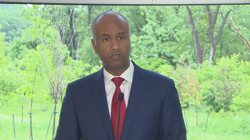 Le ministre de l'Immigration, des Réfugiés et de la Citoyenneté et député de la circonscription de York-Sud, Ahmed Hussen avec un veston bleu marine et une cravate rouge.