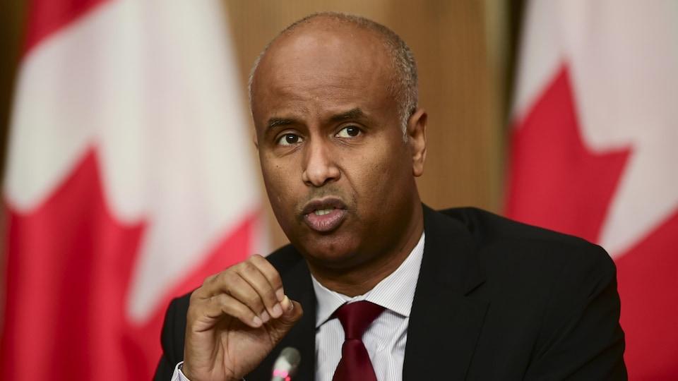 Ahmed Hussen devant deux drapeaux canadiens.