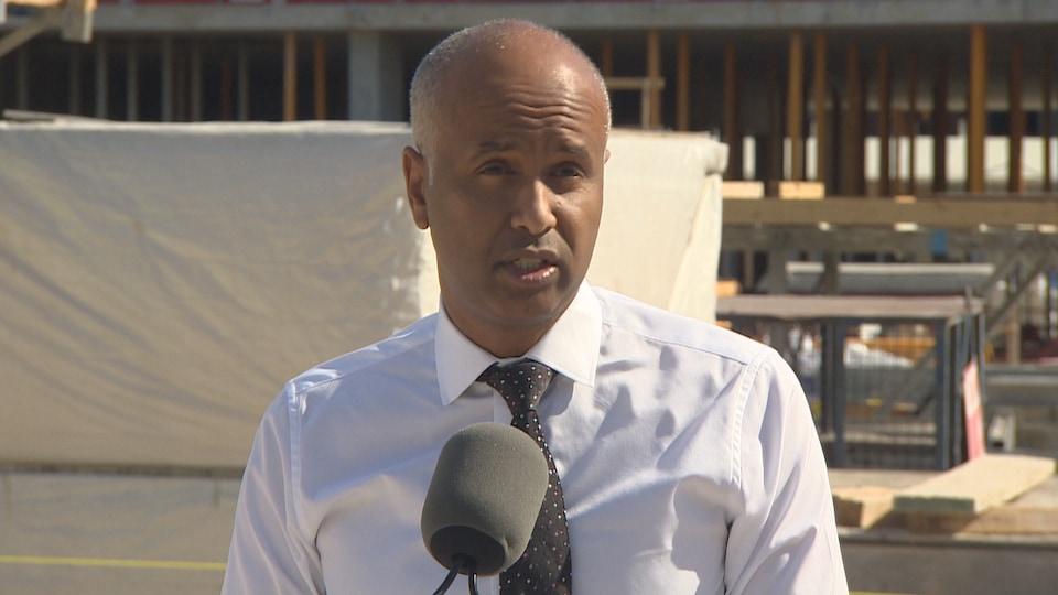 Le ministre de la Famille, des Enfants et du Développement social, Ahmed Hussen, en conférence de presse sur un chantier de construction.