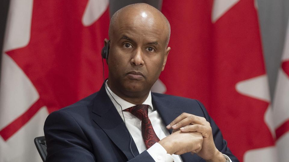 Ahmed Hussen, assis sur une chaise, écoute dans son oreillette.