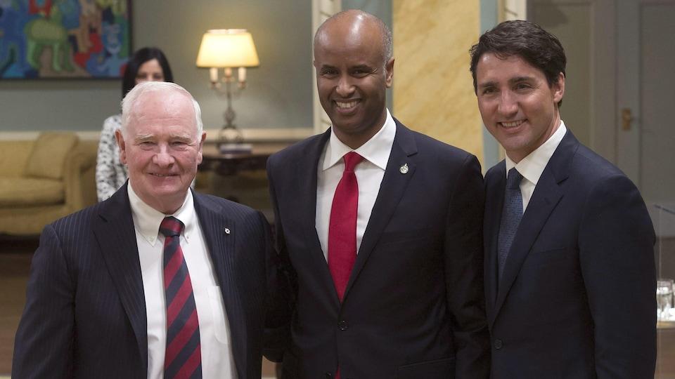 Le ministre de l'Immigration Ahmed Hussen pose aux côtés du gouverneur général, David Johnston, et du premier ministre du Canada Justin Trudeau.
