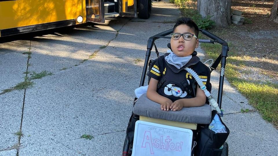 Ashton, assis dans un fauteuil roulant, à l'extérieur devant un autobus scolaire.