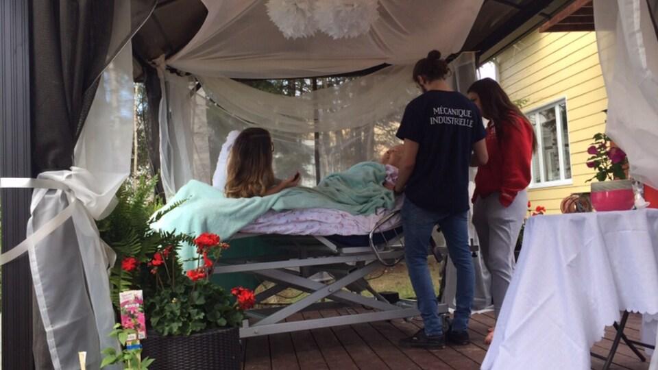 Deux hommes et une femme entourent le lit d'une femme âgée en fin de vie.