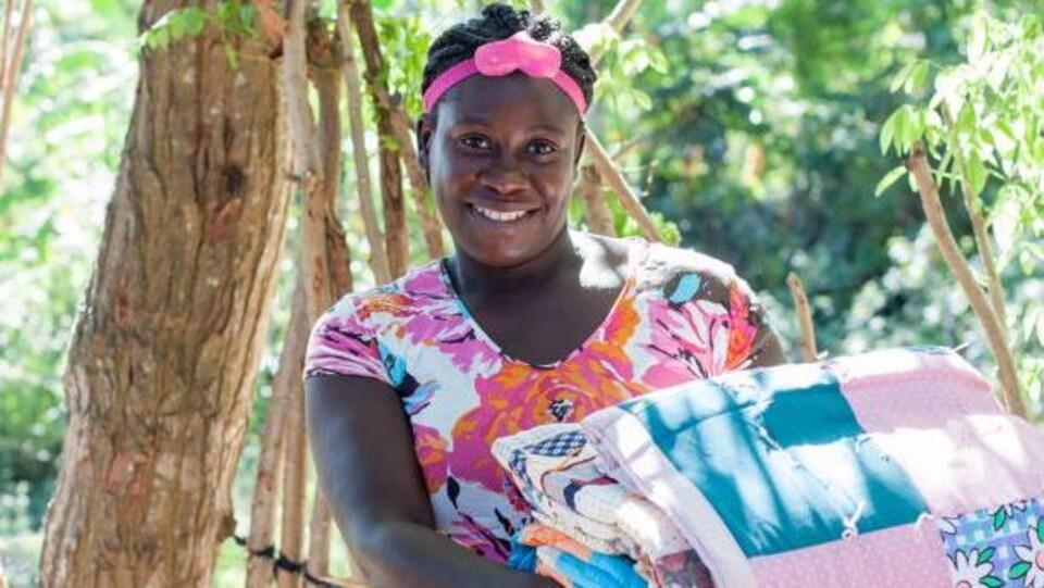 Une femme toute souriante qui tient une pile de couettes entre les mains.