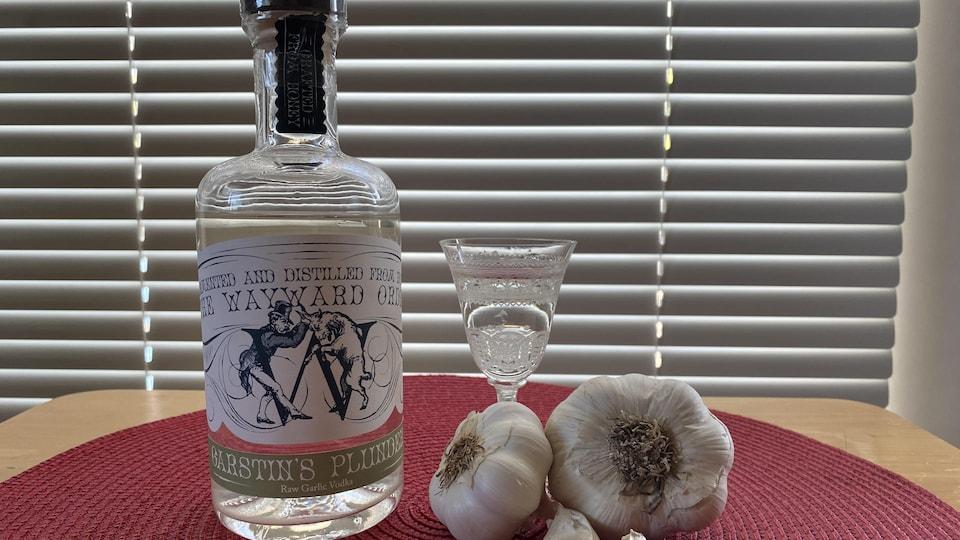 Une bouteille de vodka, un verre et des gousses d'ail sont posés sur une table.