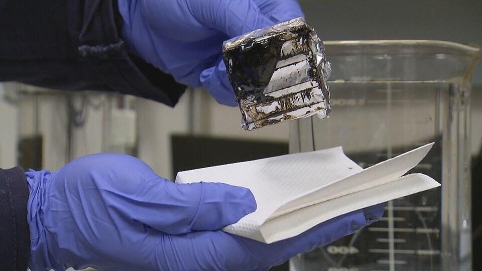 Gros plan sur les mains d'un scientifique qui porte des gants bleus. Il tient dans une main l'aimant où s'est agglutiné le pétrole. Dans l'autre, il attrape un essuie-tout.