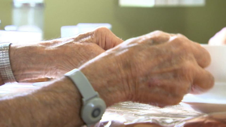 La caméra montre en gros plan les mains d'une personne âgée qui s'affaire à une table.
