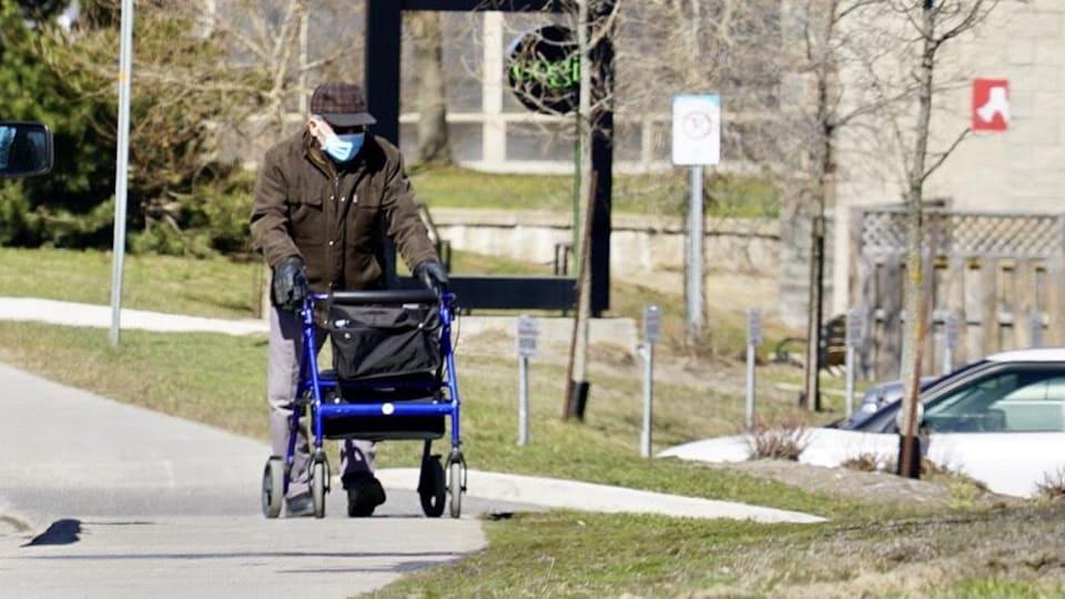 Une personne âgée marche sur le trottoir à l'aide d'un déambulateur.
