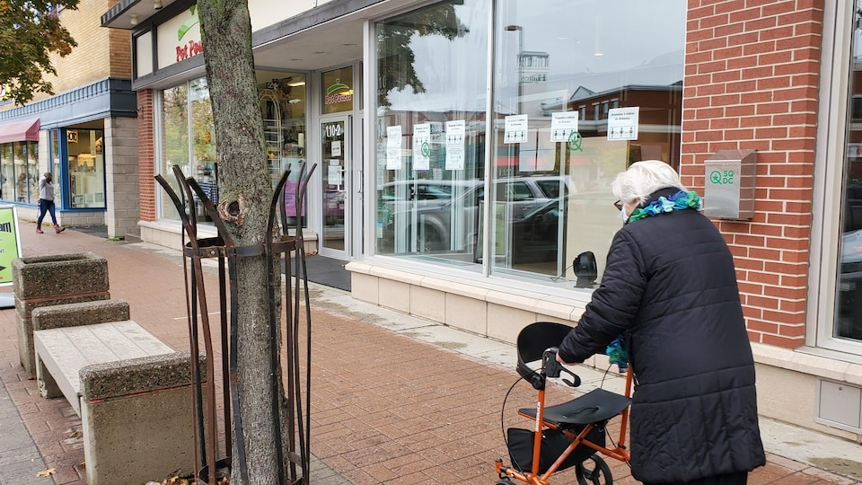 Une personne âgée marche avec son déambulateur au centre-ville de Rimouski.
