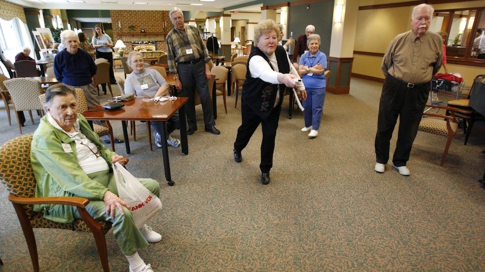 Des aînés jouent à un jeu vidéo.