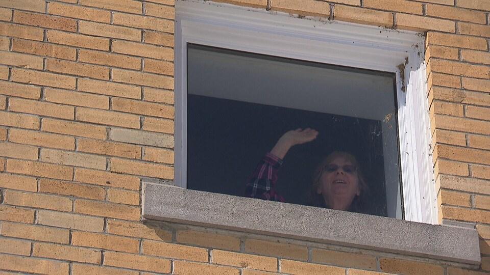 Une aînée fait un signe de la main de sa fenêtre.