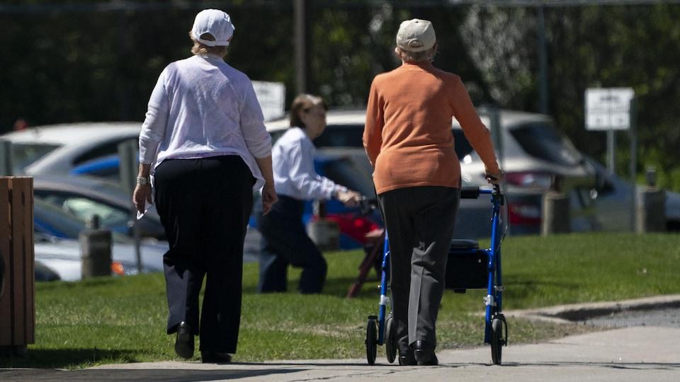 Des personnes âgées se promènent dehors.